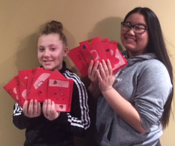 Grade 8 students Amber and Raisa hold up a bunch of valentine's to be delivered to residents