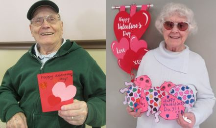 Residents Ben and Marion smile holding the valentine's they received
