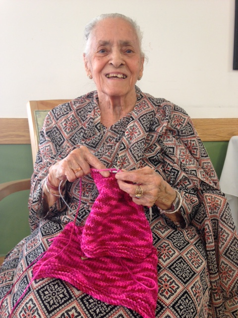 Swaran Suri sits smiling in a chair while knitting a pink outfit for a baby
