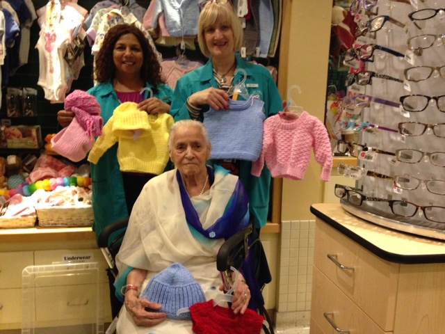 Swaran Suri is joined by two staff from SickKids Hospital and they are each holding outfits that she has knitted up for the camera