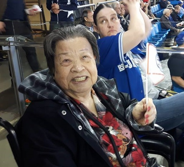 A woman sits smiling in her wheelchair, holding a Blue Jays flag, at the game