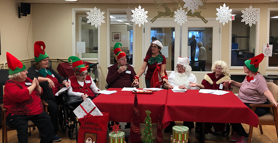 Residents of the dramatic arts club dressed as elves, practicing for a play called Santa's Cookie Problem