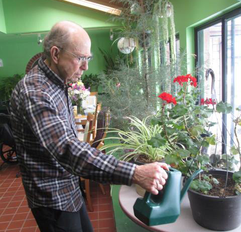 A man waters plants inside a long-term care home