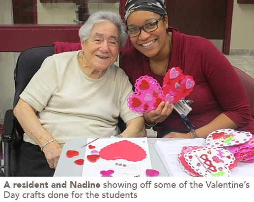 A resident and staff member show off Valentine's Day themed crafts done by the kids