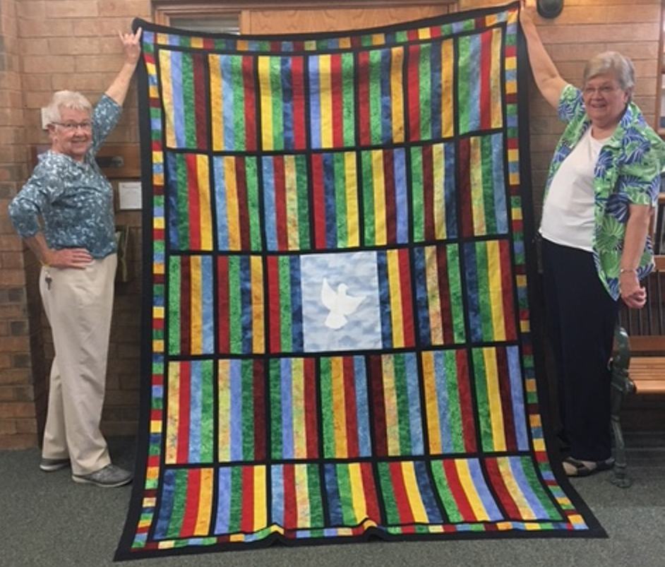 Martha Goode and Marion Kidd stand with the home's dignity quilt between them